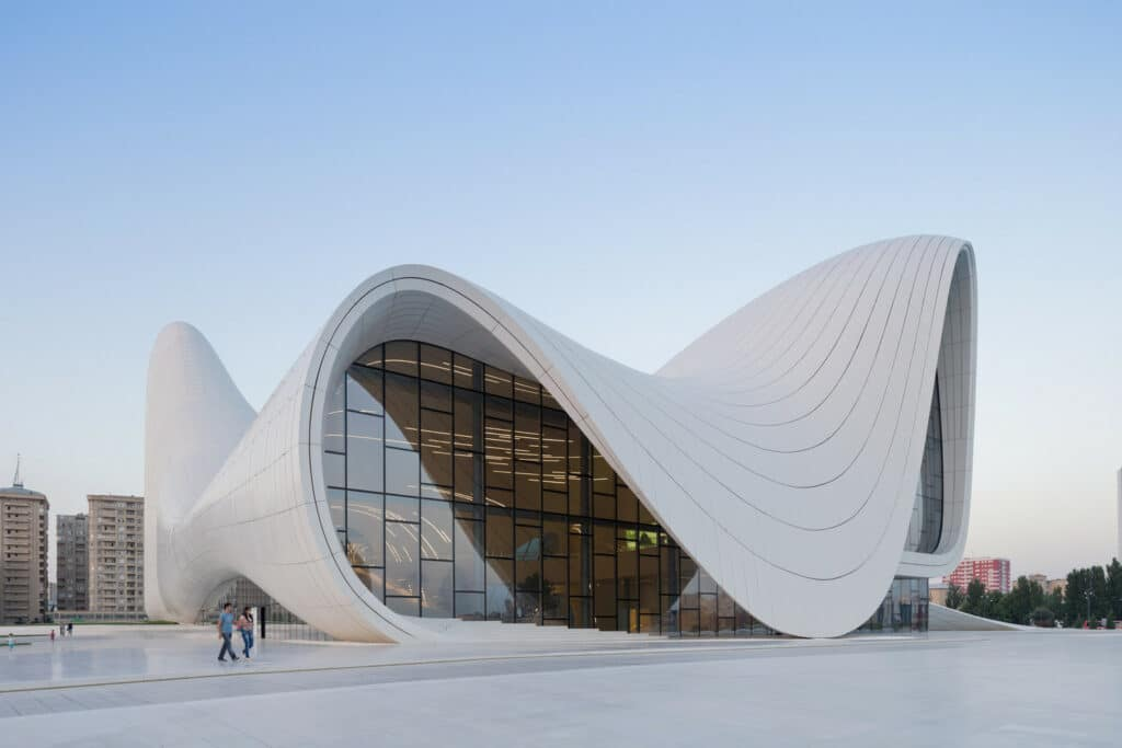 Photo of the Heydar Aliyev Center constructed by Zaha Hadid. It is a curvey white building with large windows. I seems to defy the laws of architecture the way is loops on curves.