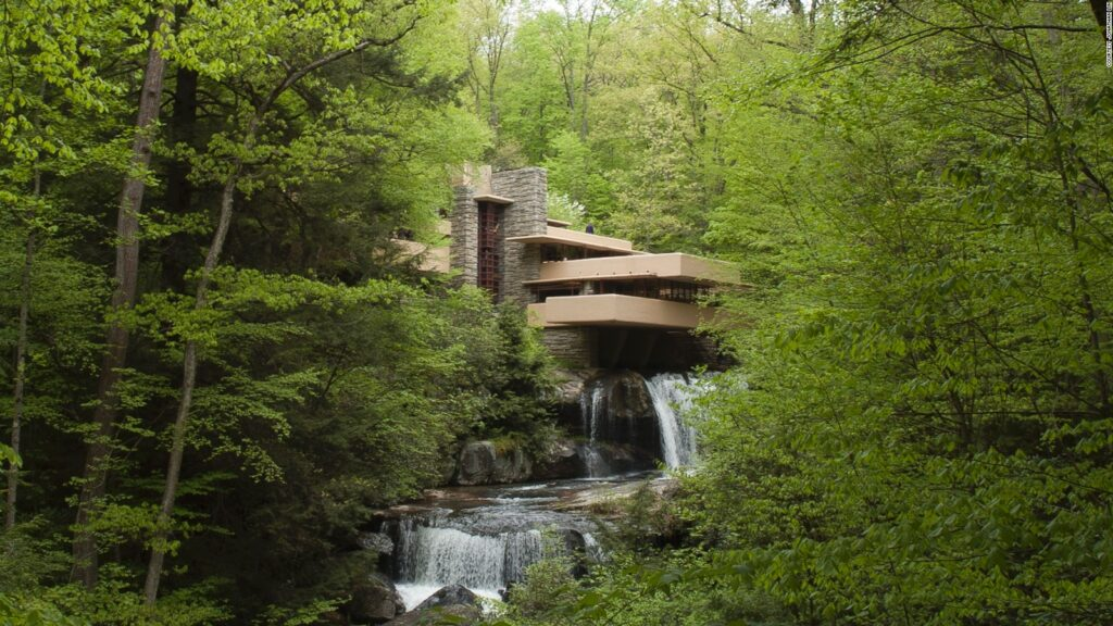 Photograph of Fallingwater residence. It is a modern building surrounded by lush greenery. A water fall spills out from under the building as if it coming from the building.