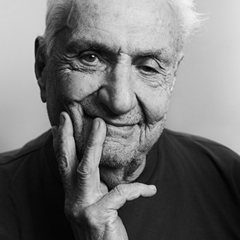 Portrait of Frank Gehry in black and white. His hand is on his face and his is smiling.