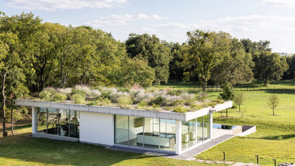 Photo of an minimalist white pool house with plants on the roof.