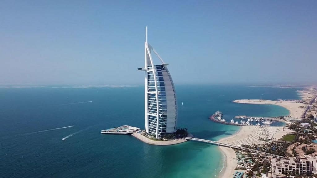 Photo of Burj Al Arab. It is a large sail structure that sits on the water front.