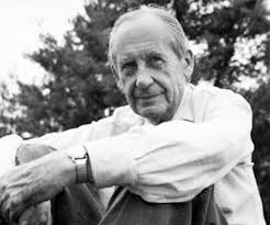 A classic portrait of Walter Gropius sitting smiling in a white dress shirt and slacks. Behind him are trees.