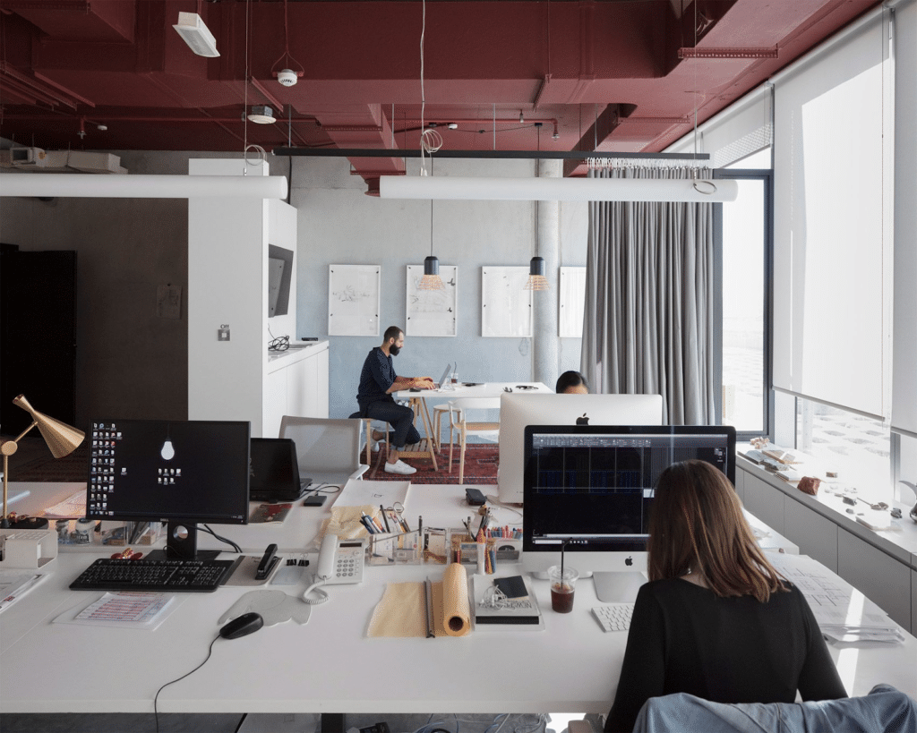 architecture office with two women and one man sitting at a white desk with computers